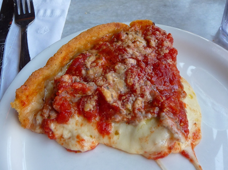 "A slice of the ""Malnati Chicago Classic"", its signature deep dish pizza with lean sausage, extra cheese and vine-ripened tomato sauce on Buttercrust."